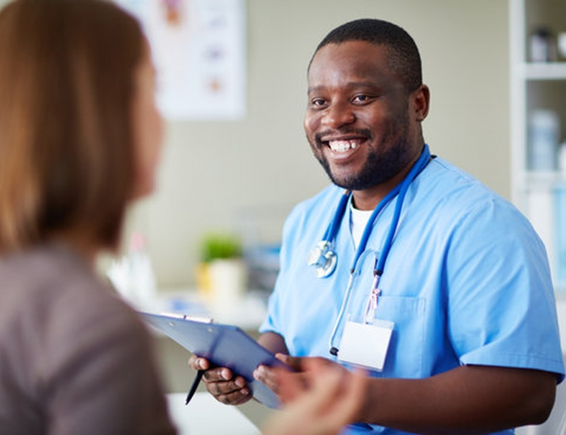 Smiling African doctor working with patient in his office